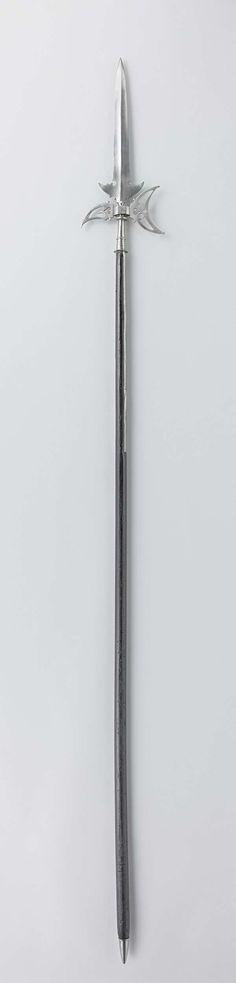   Partizaan, c. 1600 - c. 1699   Partizaan met gekartelde vleugels. Opengewerkte bijl met hart-vormige uitsparingen. Glad, zeshoekig middenstuk. Gladde schacht met ringornament. Twee lippen (51.0 cm). Aan het uiteinde van de stok een gladde, ijzeren punt. (7.0 cm)