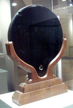 English: Aztec mirror carved from obsidian, on a modern wooden base. Museum of the Americas, Madrid.  Español: Espejo azteca de obsidiana, sobre un soporte moderno de madera. Museo de América, Madrid.
