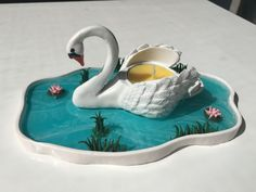 Swan lake candle holder, by Lilith Marleen. Materials: Polymer clay, wire for structure, UV resin for water effect, varnish.