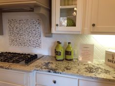 Level 2 granite, white cabinets, herringbone subway tile, warm tone hardwoods