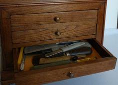 Matériel de reliure (découpe) en fouillis dans le tiroir d'une commode de maitrise