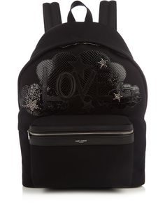 Saint Laurent decorates its essential black City backpack with leather appliqués, silver-tone star embellishments, and a 'Love' slogan for SS17.