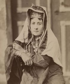 Palestinian woman from Bethlehem, 1883.  Note the details of her silver jewelry, including a triple row of habiyat bracelets and a glorious silver iznaq / chin-chan with many silver coins.