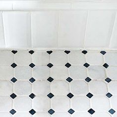 """Tile Baseboard was fashioned by turning field tiles on end and topping them with trim for a custom look at minimal added cost. Homeowner Tip: """"We browsed big plumbing showrooms for inspiration, but buying from a smaller, local dealer got us a 20 percent discount on our marble floor tile,"""" says Filip Balasov. Wall tile: Adex USA Floor tile: Marino Ceramic Tile Inc."""