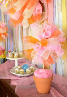 Gorgeous Deco mesh topiary sitting on what looks to be a candy/sweets bar at a party.
