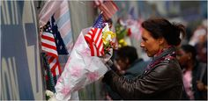 A woman hung a bouquet and a U.S. flag at the World Trade Center site in New York. Photo by Mike Segar/Reuters