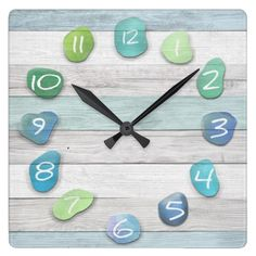 Sea Glass Beach Driftwood-effect wall clock in Grade-A acrylic material showing white numbers on pebble-like splashes of oceanic blues, turquoises and greens. (Affiliate).