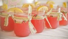 Pink lemonade in small jelly jars with vintage fabric strips.  Great touch for a warm outdoor ceremony.