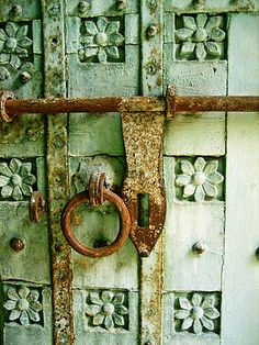 Rusty circular Knocker and bolt On carved green wooden door with flower details