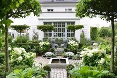 Simple water feature centered in cobblestone with formal garden surround...