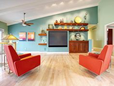 This midcentury modern living room features a pair of reddish orange armchairs, a large TV and floating wood shelves and built-in cabinets that perfectly fit the angled blue wall.