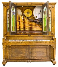"""The interior of a Seeburg G orchestrion from 1913 containing a piano, mandolin, snare drum, bass drum, timpani, cymbal, triangle, and flute and violin organ pipes."""