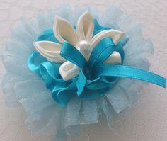 Flor totalmente artesanal, hecho de cinta azul y  organza  turquesa , decorada con una segunda de satén marfil y con un cordón nacarado, todas ellas decoradas con una pequeña cinta de la turquesa y una perla.Tamaño de la flor 8 cm