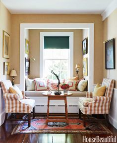 Antique chairs slipcovered in Roth & Tompkins's Lyme check flank the living room window seat.
