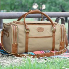 """This versatile bag is not only great to use at the gym but also as an overnight bag. Crafted with Tan Cordura®, fabric with tanned Rio Latigo reinforcement trim. This indispensable bag features two large pockets on each end with small outside zip pockets and an open pocket on each side. The large open main compartment has a durable leather bottom. Adjustable, detachable shoulder strap and brass feet to protect the bottom. 20 1/2"""" x 11"""" x 11""""."""