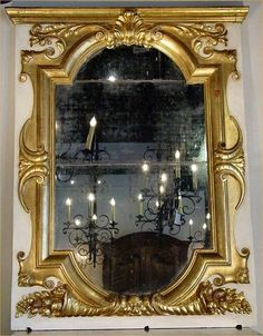 A gorgeous and important 19th century Italian patinated off white and gilt mirror. The original mirror plate is surrounded By carved gilt ornaments of two 'c' Scrolled baskets of fruits at the bottom with a masculine mask. Above is a central Acanthus leaf amidst foliate scrolls all below the moulded crown.