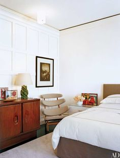 In the master bedroom of a New York apartment renovated by Shelton, Mindel & Assoc. are a 1950 Alexandre Noll console, a 1960 Poul Volther Pyramid chair, and a 1948 Georges Jouve ceramic lamp. Rudolf Koppitz's Im Schosse der Natur (1923) hangs on a wall. On the console are drawings by Le Corbusier.