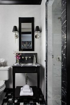 @Osborne & Little wallpaper is the perfect backdrop to this custom-made vanity with a Nero Marquina marble top. @Waterworks single-arm wall sconces in polished nickel and black shades complete the look in this art deco inspired bathroom designed by @Designer Eva Quateman