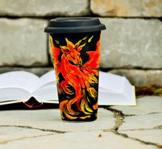 Fire Dragon Travel Mug - Dungeouns and Dragons inspired Eco cup - Black Red Yellow Hand Painted Coffee Mug with Lid - Gift for him    The perfect gift for a Dungeons and Dragons fan or a lover of dragons and fairy tales, this travel mug will let you hold fire without burning your hands. Get it personalized at no extra cost.    This cup is a great Eco-friendly alternative to paper. Its double-walled insulated design keeps your hot beverages hot, and cold ones cold. It also makes it easy to…