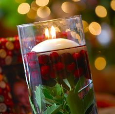 Hurricane vase with a floating candle, cranberries and holly. Easy and so beautiful!
