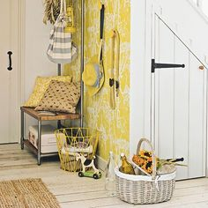 Hallway with pale wood floorboards, yellow wallpaper feature wall and sisal rug