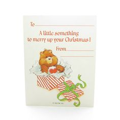 """This vintage Care Bears gift tag card features Tenderheart Bear popping up out of a red and white striped box, the lid of the box is wrapped with a green bow. The gift tag says """"A little something to"""