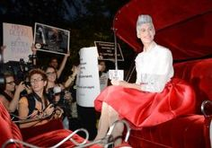 Models in horse-drawn carriages booed by animal rights activists