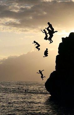 Silhouette of kids jumping off a cliff into the water