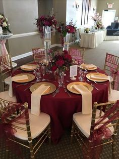 This gorgeous table set up is filled with upgrades! Floor length Burgundy table cloth, champagne napkins, gold charger plates, gold chiavari chairs and burgundy chair sashes #champagne_gold_decor