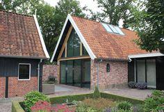 Een grote glazen pui, houten gebinten en een lichtstraat in het dak. Busscher Serrebouw / www.busscher-serres.nl