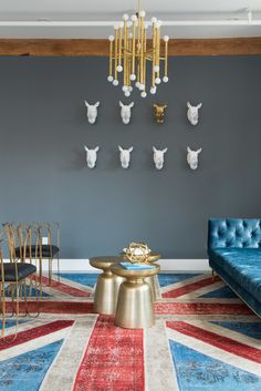 Eclectic Minimalist Wall Treatment: Cast sculptures mounted behind chandelier and vibrant decor..