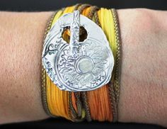 (http://2littleps.com/blog/)  Silk Wrap Bracelet  This hip toggle kissed by the sun is hand crafted from reclaimed silver. Shimmering in the summer sun, this sun kissed toggle is interlaced with a hand dyed silk ribbon with golden hues of a summer harvest that wraps end over end around your wrist. The gentle sari wrap is generous, and flowing in grace and comfort just like a carefree summer day.The artisan toggle ornament is crafted from pure fine, environmentally friendly silver and is 99%…