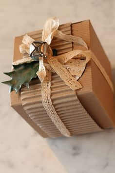 Corrugated card and a lacy ribbon for texture with a dangling silver bell & holly leaf #giftwrapping