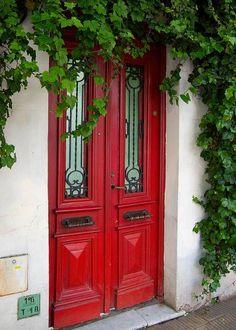 Entrée verdoyante accentuée par une porte rouge