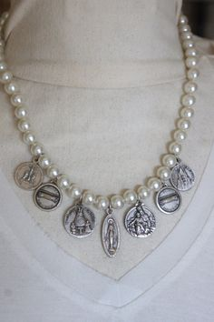 A strand of vintage 1960s faux pearls is now adorned with seven vintage medals from Europe. The are in beautiful condition and have lovely detailing. This necklace lays like a bib style necklace and is lovely on. It is finished off with my signature ornate jewelry hook. All handmade and one of a kind. Pearl necklace length: 16 Length to end of longest medal: 18 1/2 ***Please read the link below on my shop policies*** https://www.etsy.com/shop/frenchfeatherdesigns&#x...