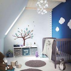 Un mur peint en bleu nuit vient sublimer cette chambre bébé fille mansardée. Et pour un univers encore plus remplit de rêves, des formes nuages sont disposées sur le mur ou encore sur le lustre. Des stickers muraux en relief viennent quant à eux créer de toute pièce un monde imaginaire et créatif fait d'arbres, d'étoiles et de chouette. Des notes de mauves toutes en nuance viennent égayer la pièce en la féminisant. La chambre parfaite pour les petites princesses rêveuses !