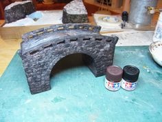 石橋の塗装はモデリングペーストでの下塗りが完了して、タミヤのアクリル塗料を使って進めます。 使用カラーはフラットブラックとレッドブラウン(もしくはハルレッド)。石=グレーを使いがちですが、よく観察すると時間の経過した石は結構黒っぽいもの。この2色で十分です。溶剤で薄く希釈してそれぞれの石に変化が出るようにわざとムラに成るように塗装していきます。黒っぽい所があったり茶色っぽい部分があったりと。