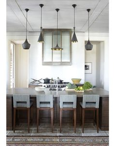 Hamel hung three different styles of Tom Dixon Beat lights over the large island, made of oak and Lagos Blue CaesarStone. He designed the barstools.