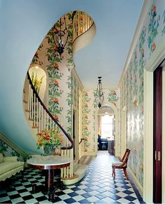the contrast of these patterns and colours remind me of alice in wonderland it looks great the sky blue ceiling representing the sky,the vine patterned wallpaper running up the wall and the classic black and white tiles on the floor just to top it off.