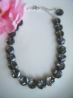 This glamorous necklace is designed with black crystallized glass beads alternating with sterling silver beads between.