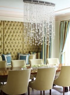 Love the tufted upholstered wall behind the bench and the cascading chandelier. Design by @Tobi Fairley