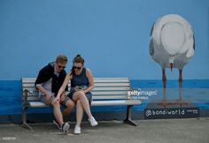 A couple sit in front of street art on Bondi beach on a stormy day in Sydney on March 8, 2017. Hundreds of weather records tumbled as Australia endured a summer of extreme events, scientists said on March 8 with climate change tipped to increase the frequency and severity of such phenomena. /