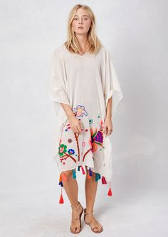 Beautiful, vibrantly colored hand embroidered caftan with double V-neck detail and multi-colored tassels. Perfect for over a swimsuit at the beach! Self: 100% Cotton Model is 5'10, wearing Off White,