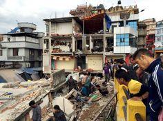 Massive earthquake hits Nepal. People survey a site damaged by an earthquake in Kathmandu.