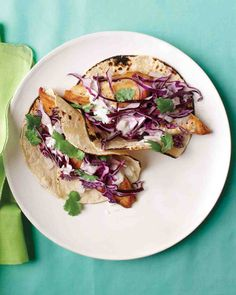 Fish tacos often involve deep-frying and heavy sauces. These are fresher and lighter, with crunchy cabbage, cilantro, and a creamy lime-infused sauce topping broiled tilapia.