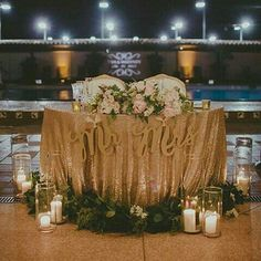 Sweetheart table. White table cloth. Rose petals and short candles on table. Candles and lanterns surrounding table.