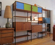 MID CENTURY MODERN FREESTANDING IRON FRAMED BOOKSHELVES COME WITH GREEN AND BLUE SLIDING DOORS TOP STORAGE BOXES AND WOODEN CENTER 3 STORAGE DRAWERS AND OPEN STORAGE SHELVES ALONG WITH LARGE PULLOUT FILE DRAWERS