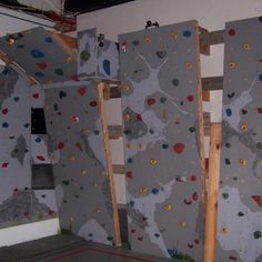 Home made rock climbing wall: red wall with black and grey rocks!