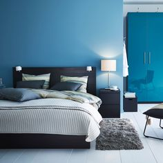 A modern blue and black bedroom with MALM bed in black and PAX wardrobe in…