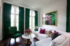 deep emerald draperies & chair L shaped couch in white white & round top center table white walls magenta accent pillows dark toned wood floors of The Collections of Impressive Interior Decorator Houston for Homes